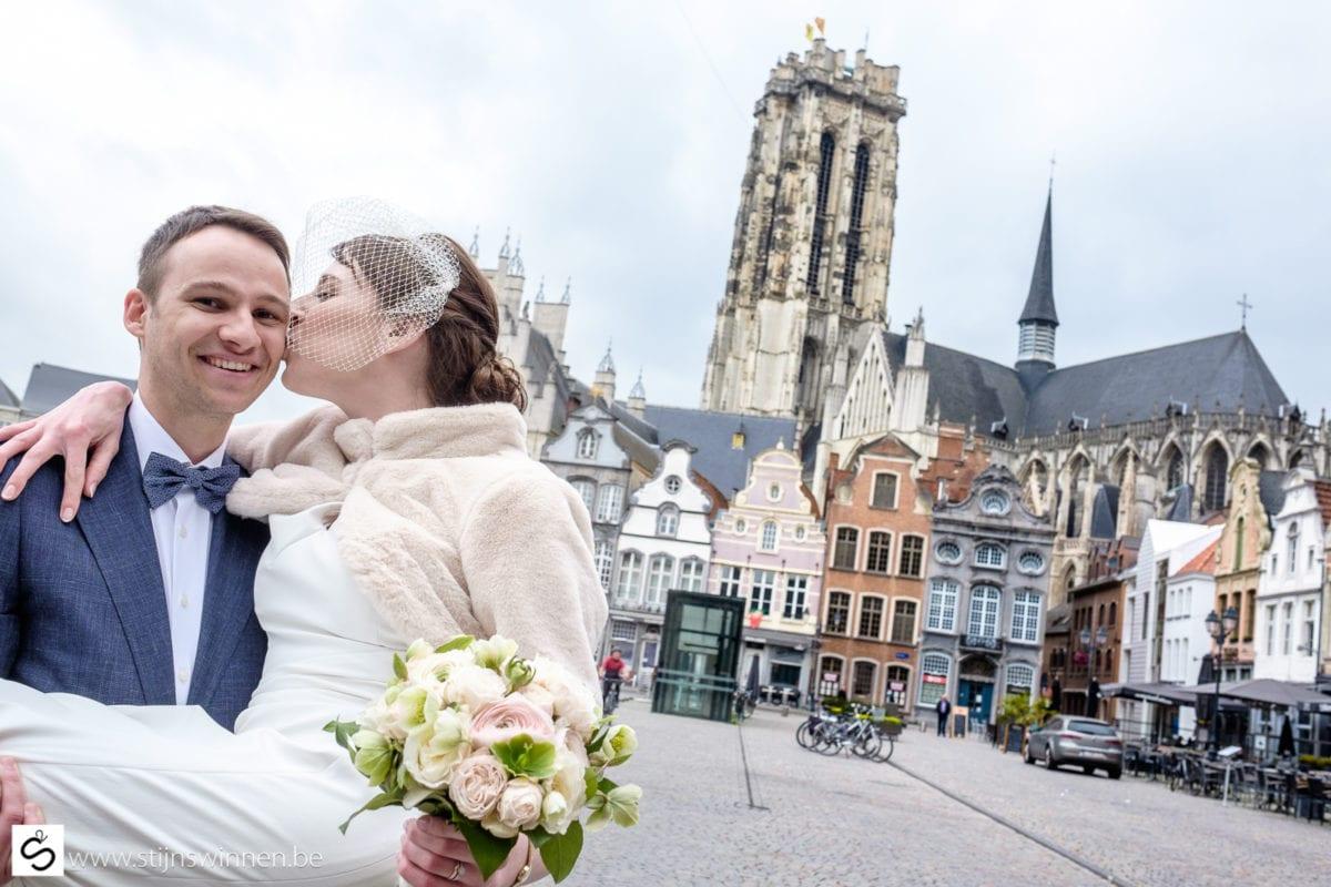 Huwelijksreportage in centrum Mechelen met op achtergrond de lege Grote Markt en Sint-Romboutstoren