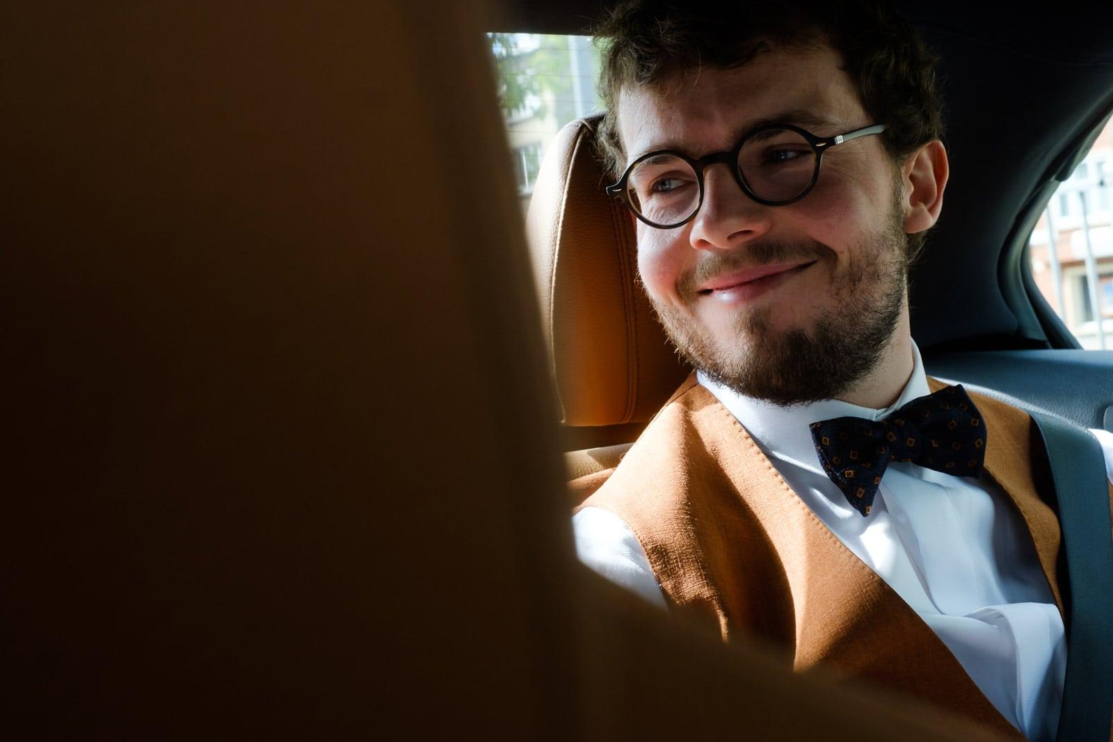 Bruidegom kijkt met verliefde blik naar bruid in de auto.